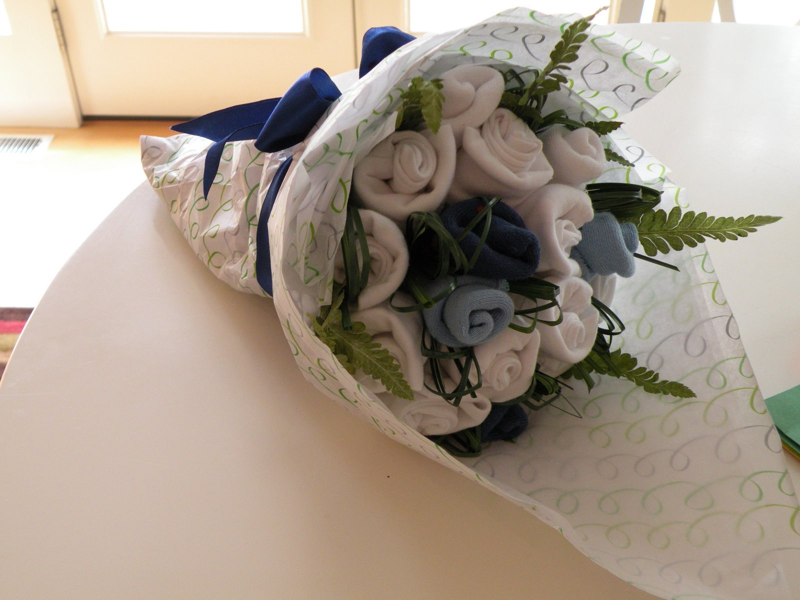 Socks onesies bouquet jens blossoms blog this bouquet was for a baby boy what you cannot see is that the handle of the bouquet is wrapped in chocolate brown ribbon and tied with a bow izmirmasajfo